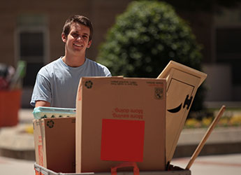 Male student with move-in cart filled with boxes during move-in days.